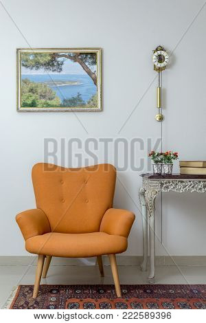 Vintage Furniture - Interior composition of retro orange armchair, vintage wooden beige table, and pendulum clock over off white wall, tiled beige floor and orange ornate carpet
