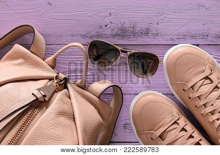 Womens Accessories And Footwear (leather Backpack And Sneakers, Sunglass) On Violet Wooden Backgroun