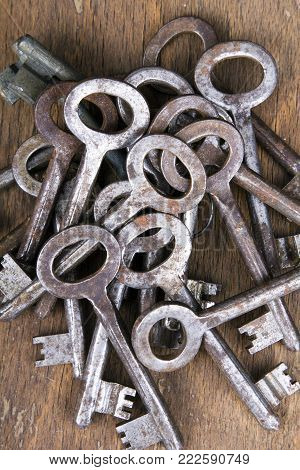 Old rusty keys on wooden background, top view