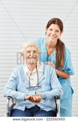 Young nursing woman or nurse and smiling senior citizen in wheelchair
