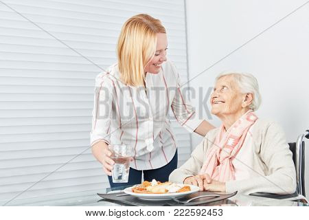 Young woman serving senior citizen a lunch or dinner at the retirement home
