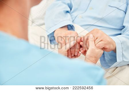 Nursing lady holds the hands of a patient in the hospice as a terminal care