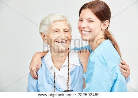 Smiling nursing assistant and happy senior woman hugging each other in nursing home