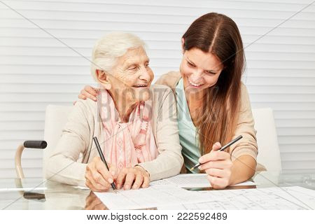 Girls as a caring grandson and senior together solve puzzles in retirement home