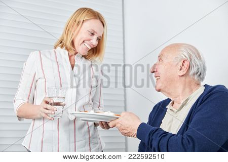 Nursing Woman brings a meal and a glass of water to old man