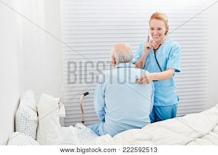 Woman as a doctor examines the breathing of a sick senior with the stethoscope