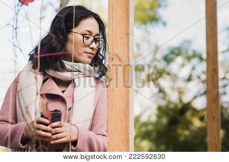 Beautiful young asian woman drinking hot drink from disposable paper cup outdoors. Girl dressed in pink coat and white scarf. Look down.