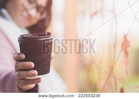 Beautiful young asian woman drinking hot drink from disposable paper cup outdoor. A girl with glasses. Asian woman giving hot coffee or tea to camera.