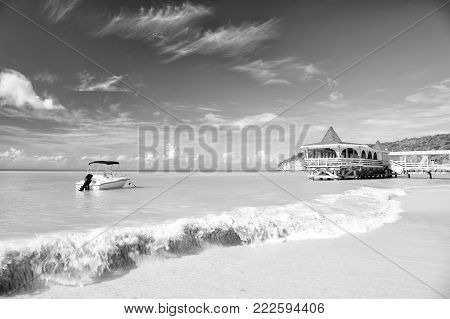 motorboat, yacht on sea water of ocean coast with wooden cafe building in bay sunny summer outdoor on blue sky background in St. John, Antigua, traveling and vacation, sport and sailing