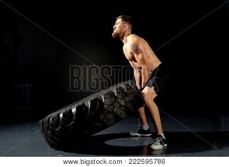 Athletic training. Muscular man flipping tire at gym