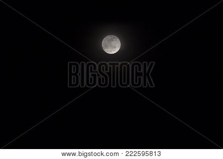Full moon on dark night sky. Skyscape with moon phase in equator. Black and white night sky photo. Moon relief. Space light in darkness. Cosmic banner template of celestial object on black