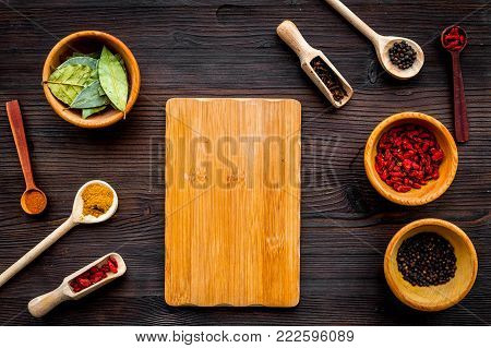 Make menu or write recipe. Mock up for menu or recipe. Wooden cutting board near spices and ingerdients in spoons and bowls on dark wooden background top view.