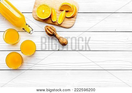 Make orange juice. Juicer, beverage in bottle near slices of oranges on white wooden background top view.