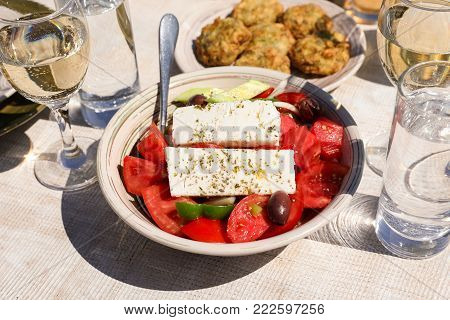 A bowl of village greek salad next to zucchini balls plate and white wine, water glasses served in greek tavern. Horizontal. Daylight. Close-up.