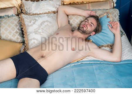 Man With Present Boxes Lie On Bed In Bedroom