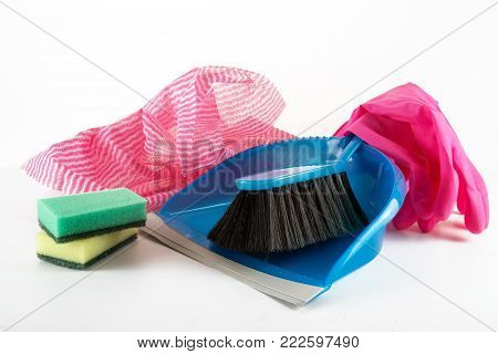household utensils for the spring cleaning, dustpan and hand brush, cleaning rags, sponges and rubber gloves, light gray background, copy space, selected focus