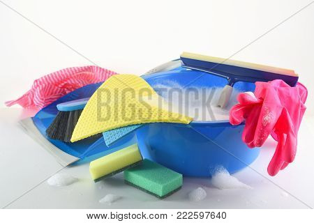 Spring cleaning equipment, blue plastic bowl with soap foam, pink rubber gloves, rags, sponges, window wiper, dustpan and brush on a light gray background with copy space, selected focus, narrow depth of field