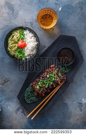 Asian style bbq pork ribs with sauce and rice on wooden board, top view.