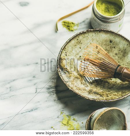 Flat-lay of Japanese tools for brewing matcha green tea. Matcha powder in tin can, Chashaku spoon, Chasen bamboo whisk, Chawan bowl over marble background, selective focus, copy space, square crop