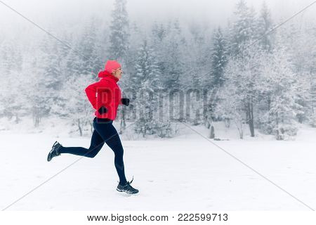 Trail Running Woman In Winter Mountains