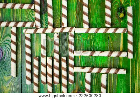 An abstract food pattern of cookies in the form of chaotically spread out tubules on a green wooden background. View from above. Close-up.
