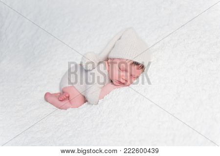 Newborn sleeping tenderly on soft bed