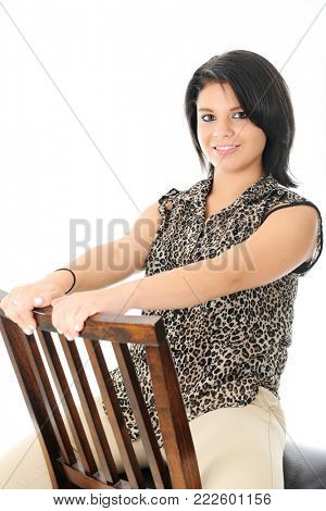 A beautiful teen girl happily sitting backwards on a wooden chair.