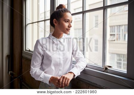 Young woman with hair bun looking out of window, waist up