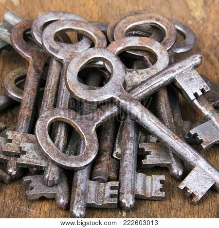 Old rusty keys on wooden background. Copy space