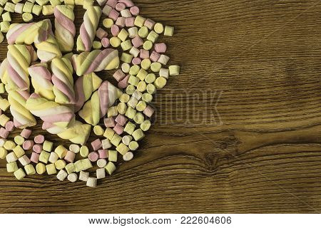 marshmallow Candies placed in the center of other candies. valentine's day and love concept on wooden background