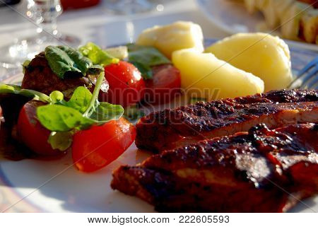 Delicious traditional crispy BBQ, tomatoes and potato