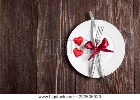 Valentines day table setting romantic dinner marry me wedding with plate fork knife on dark background with copyspace. Love gift woman making proposal romantic holiday wedding