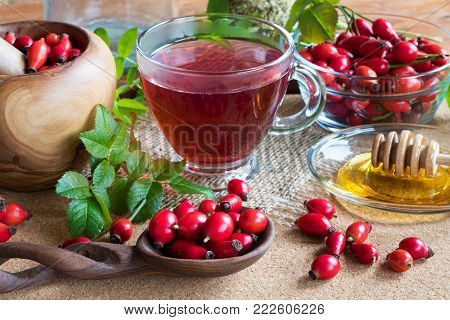 Fresh rose hips, rose hip tea and honey on a wooden table