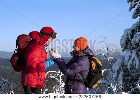 Two hikers on top of the mountain on a clear frosty day against the backdrop of a forest landscape in the valley; a woman offers a man a hot tea in a cup (in a thermos cap).
