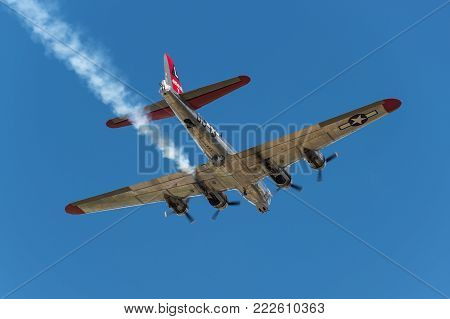 EDEN PRAIRIE, MN - JULY 16 2016: B-17G bomber Yankee Lady flies overhead with smoke trail at air show. This B-17 was a Flying Fortress built for use during WW II but never flew in any combat missions.