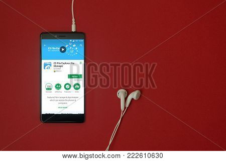 Los Angeles, January 11, 2018: Smartphone with ES File explorer file manager application in google play store on red background with earphones plugged in and copy space