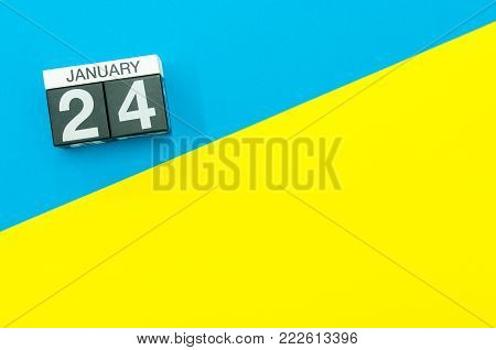 January 24th. Day 24 of january month, calendar on blue and yellow background flat lay, top view. Winter time. Empty space for text.