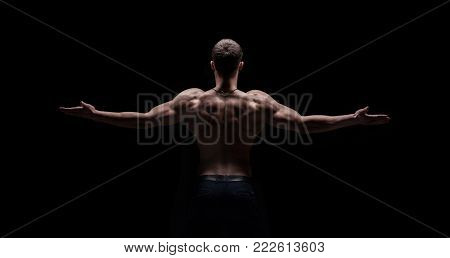 shirtless strong athletic mans back on black background
