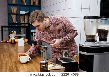 Young handsome barista hipster making coffee for his clients in the cafe.