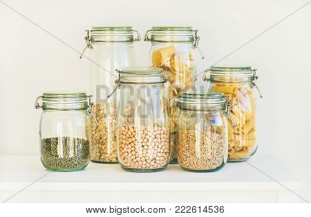 Various raw cereals, grains, beans and pasta for healthy cooking in glass storage jars on kitchen shelf, white background. Clean eating, vegetarian, vegan, balanced dieting food concept