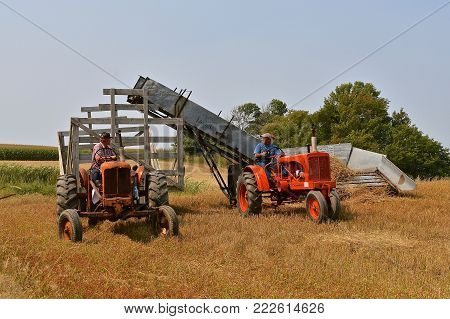 ROLLAG, MINNESOTA, Sept 2, 2017: Old Allis Chalmers tractors and an Acme Loader are harvesting grain in a field demonstration at the annual WCSTR farm show in Rollag held each Labor Day weekend where 1000's attend.
