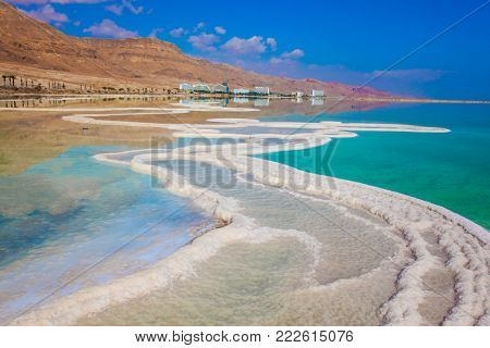 Dead Sea, Israel. Reduced water in the very salty Dead Sea. The evaporated salt is precipitated by picturesque stripes in shallow water. The concept of medical and ecological tourism.