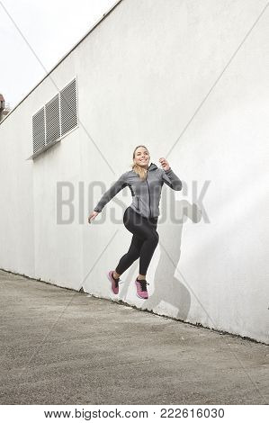 One young woman, jumping in mid-air, outdoors, white wall behind, simple minimalistic, sport clothes.