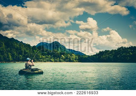 Fisherman sitting in bellyboat and fighting with big trout on lake in Jesenice, Slovenia. Still water fly fishing and outdoor lifestyle theme. Moody, contrasty, toned and faded look.