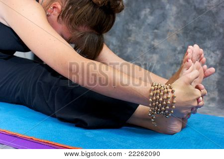 Close up of a woman's hands and feet as she bends over in a yogic forward fold or Paschimottasana on yoga mat in studio wearing mala beads. poster