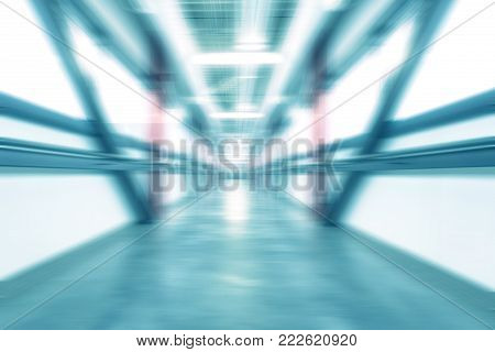 A futuristic tunnel image created with a blurring and zooming effect. A cool blue hue has been applied.