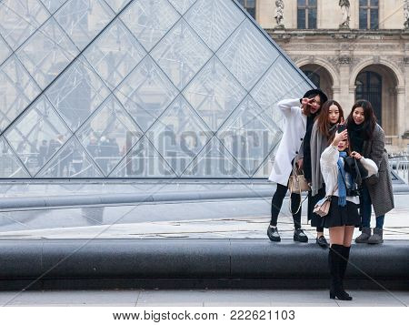 PARIS, FRANCE - DECEMBER 20, 2017: Chinese tourists taking selfie photos in front of the Louvre Pyramid. Louvre pyramid (Pyramide du Louvre) is one of the main attractions of Paris, attracting a growing number of Asian tourists