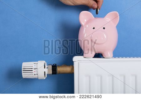 Close-up Of Person Man Inserting Coin In Piggy Bank Kept On Radiator