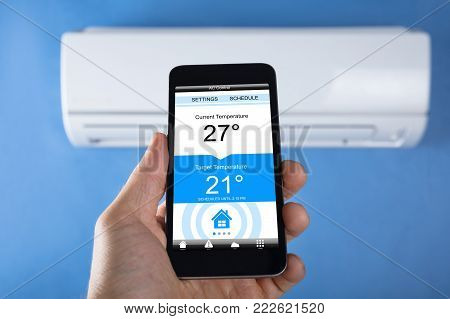 Close-up Of Person Hand Setting Temperature Of Air Conditioner Using Mobilephone At Home
