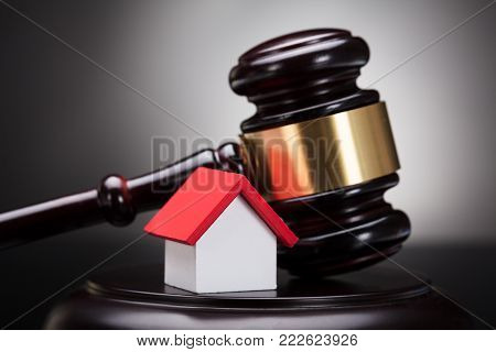 Close-up Of Gavel And House Model On Sounding Block Against Grey Background